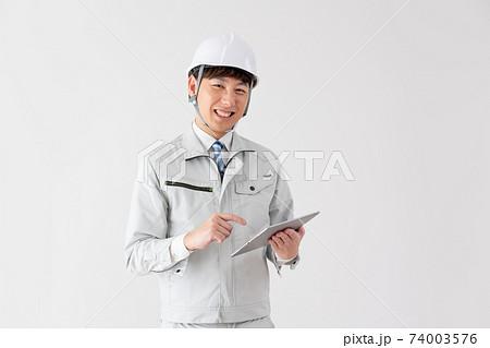 白バックのタブレットを確認する笑顔の若い作業員 74003576