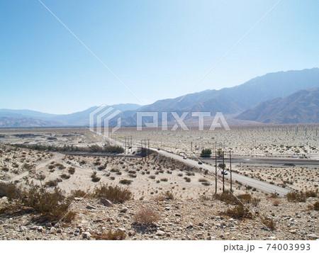 晴天のカリフォルニアの砂漠を横切る道路 74003993