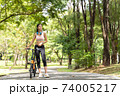 Healthy asian women with headphones on the neck are ride bike in the garden during workout at the park with blur bokeh background in sport and healthy concept with copy space. 74005217