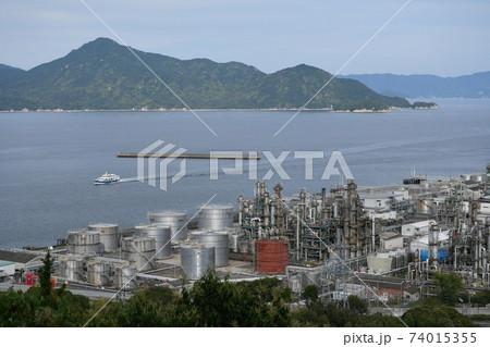 広島県大竹市小方の市道から見た、三菱ケミカルを中心とした工場と旅客船 74015355