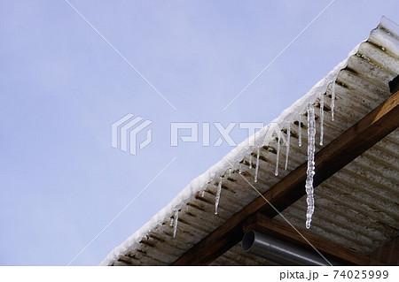 トタン屋根から垂れる大きなつらら 74025999