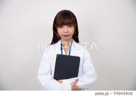 白衣を着てタブレットを抱えて正面を向く若い女性 74043916