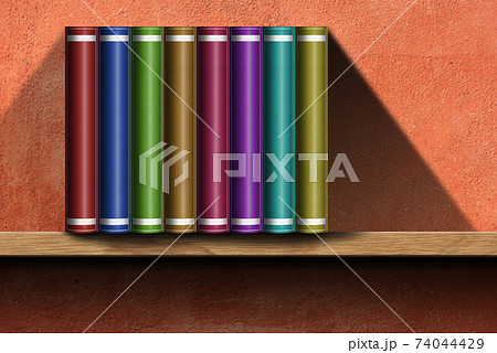 Multi Colored Books on Wooden Shelf with Orange Wall on Background 74044429