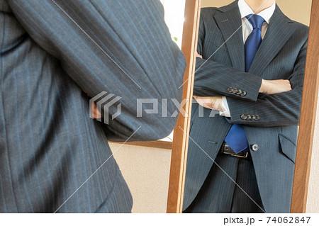 鏡の前で腕を組むスーツ姿のビジネスマン 身だしなみチェックイメージ 74062847