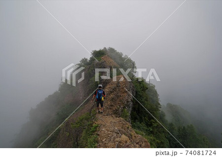 霧に包まれる戸隠山の蟻の塔渡りを歩く登山者 74081724