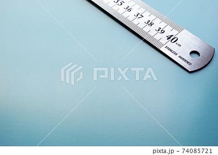 青い紙の右上に斜めに置いたステンレスの物差し 74085721