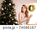 Portrait of a young pretty and dreamy blonde woman with a silver dress against the backdrop of the Christmas tree. 74086167