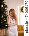 Portrait of a young pretty and dreamy blonde woman with a silver dress against the backdrop of the Christmas tree. 74086170