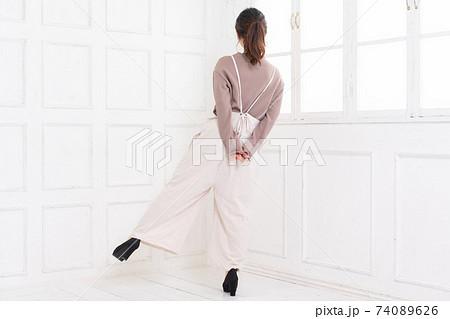 白い部屋に立ってポーズをとる若い女性 74089626