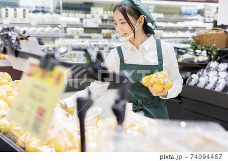 スーパーで品出しをするマウスシールドをした女性従業員 74094467