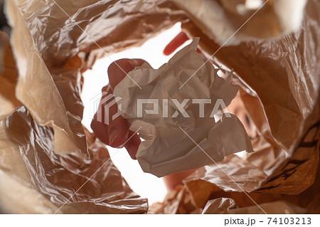 紙袋にゴミを捨てる女性(袋の中から) 74103213