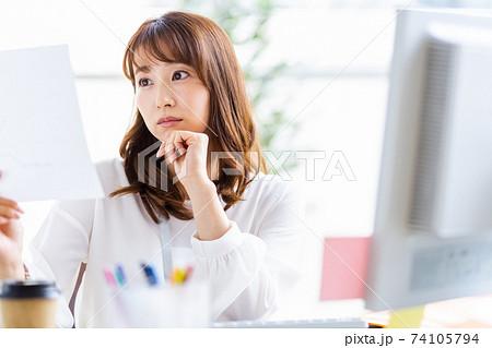 頬杖をついて紙資料を見るデスクワーク中の女性 74105794