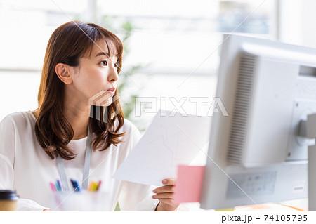 紙資料を手にパソコンのディスプレイを見るデスクワーク中の女性 74105795
