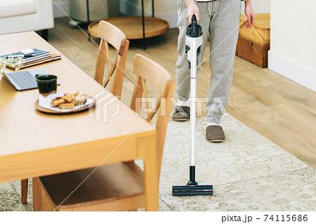自宅のリビングで掃除機をかける女性 74115686