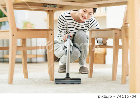 テーブルの下で掃除機をかける女性 74115704