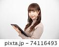 タブレットを持ちカメラ目線で微笑む若い女性 74116493