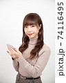 スマホを持ちカメラ目線で微笑む若い女性 74116495