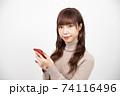 赤いスマホを持ちカメラ目線で微笑む若い女性 74116496