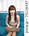 ソファーに座りパソコンをしながらカメラ目線の若い女性 74116497