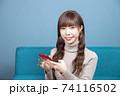 ソファーに座りスマホをしながらカメラ目線で微笑む若い女性 74116502