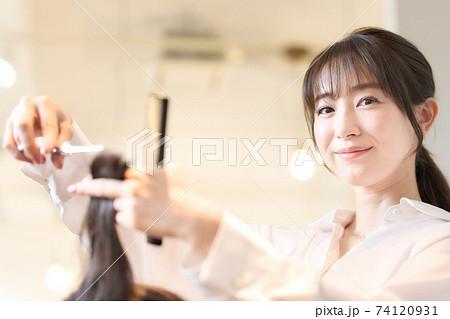 お客の髪を切るヘアスタイリスト 74120931