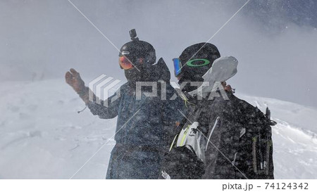強風の雪山稜線上で状況を確かめているスノーボーダー 74124342