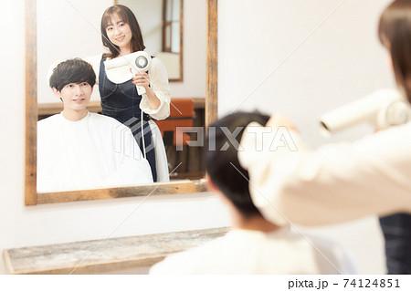 スタイリストに髪を乾かしてもらう男性客 74124851