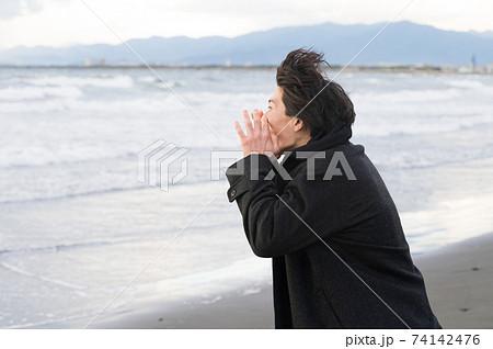 冬の江ノ島の海に向かって叫ぶ男性 74142476