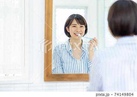 洗面所で歯を磨く若い女性 74149804