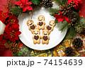 ポインセチアと松ぼっくりを載せたクリスマス用テーブルコーディネートのジンジャークッキー 74154639
