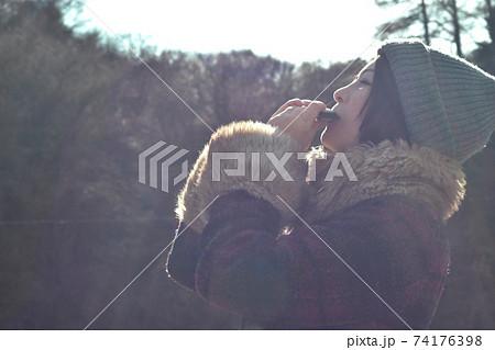 ハーモニカを吹く女性 74176398