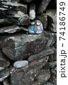 石積にそっと置かれた猫の顔が描かれた石のお雛さん 74186749