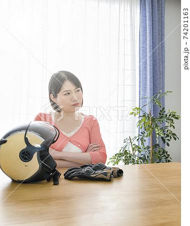 ヘルメットを置いて腕組みをする怒った表情の女性 74201163