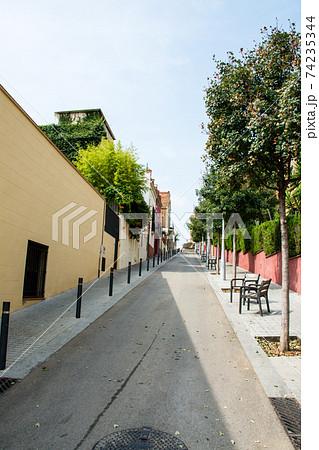 スペインバルセロナの街並み 坂の一本道の両脇に並ぶクリーム色の壁の建物とあずき色の壁 74235344