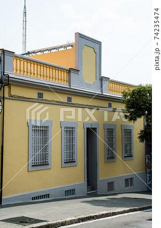 スペインバルセロナの街並み坂道に建つ格子の付いた窓とクリーム色の壁の建物 74235474