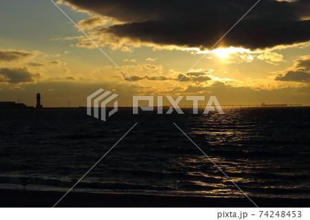 空港に近い雲から太陽が覗く夕方の浜辺 74248453