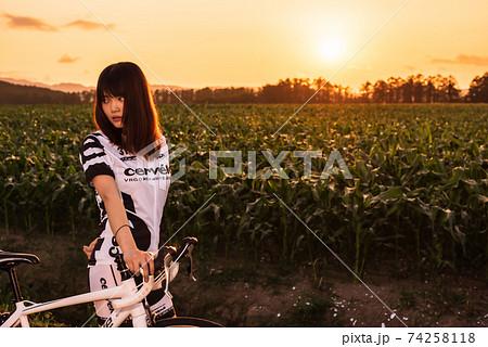 夕焼けに染まるサイクルウェアの女性ロードレーサー 74258118