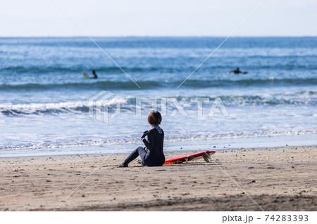 海岸で準備体操をする女性サーファーと沖のサーファー 74283393