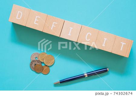 赤字|「DEFICIT」と書かれた積み木ブロックとお金とペン 74302674