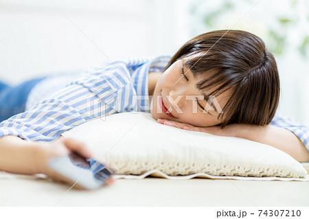 スマホを持ちながら寝落ちする女性 74307210