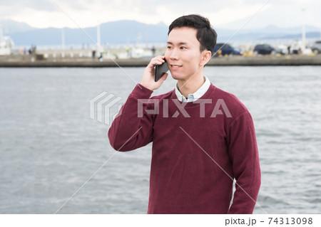 江ノ島の海をバックにスマホで通話する男性 74313098
