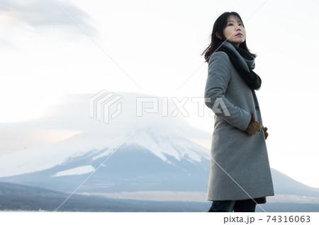 夕暮れの富士山をバックにポーズを取る女性 74316063