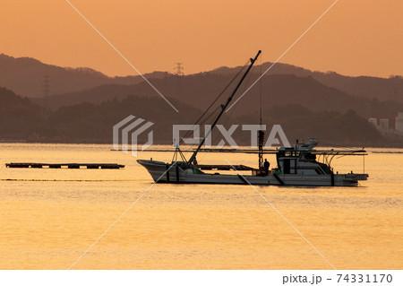 瀬戸内の冬の朝 朝焼けの海で牡蠣漁 74331170