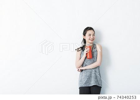 若い女性 スポーツウェア 休憩 水分補給 白バック 74340253