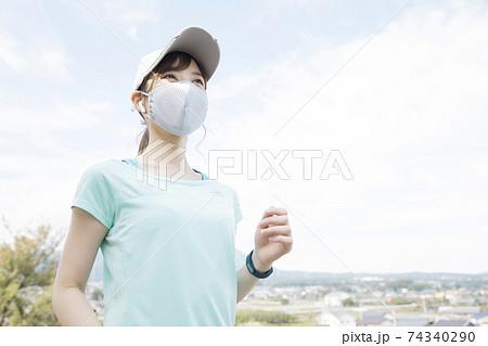 マスクをしてランニングする若い女性   74340290