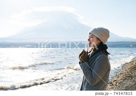 冬の山中湖湖畔でスマホを持って景色を見つめる女性 74347815