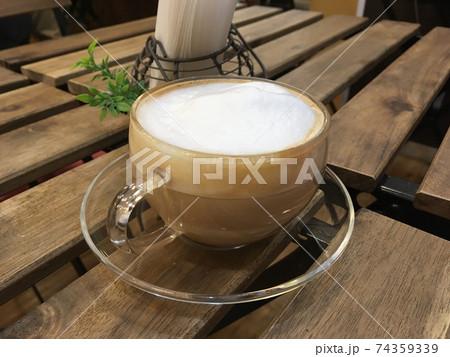 カフェのお洒落な木製の机の上にあるカフェラテ 74359339