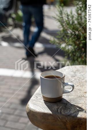 テラスに置いてあるマグカップに入ったホットコーヒー(縦暗め) 74367542