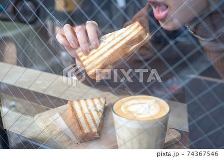 カフェでカフェラテとサンドイッチを食べる女性 74367546