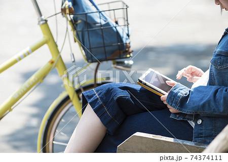ベンチでタブレットを操作する若い女性 74374111